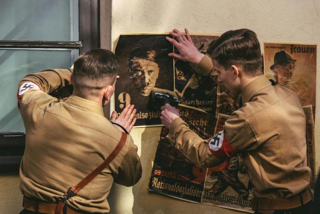 Stormtroopers in uniforms put up Adolf Hitler posters