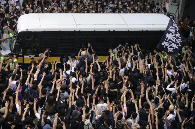 Supporters surround a police bus carrying political activist Edward Leung as it leaves the High Court in Hong Kong