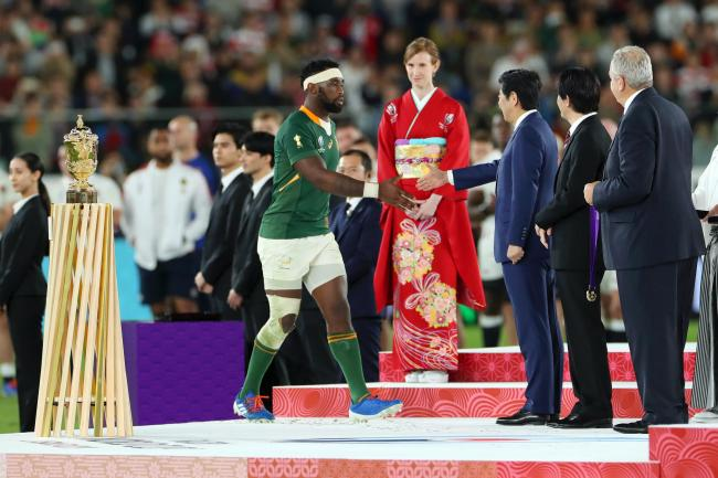 Claire Birchmore (red kimono) stands tall over Siya Kolisi, captain of South Africa, and Shinzo Abe, Prime Minister of Japan