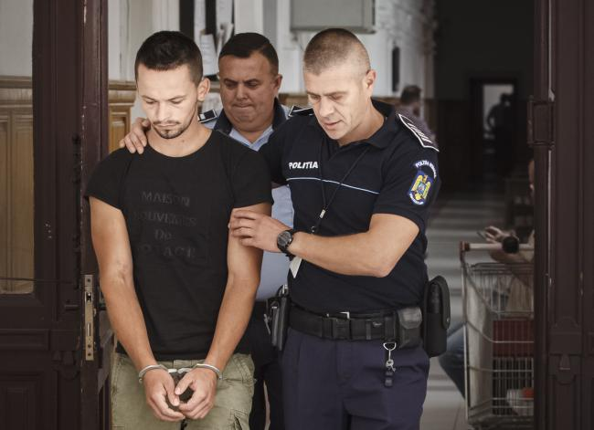 Cristian Sabau is escorted by an officer after a hearing to confirm his European Arrest Warrant