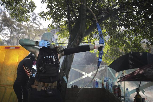 A protestor prepares to fire a bow and arrow during a confrontation with police at the Hong Kong Polytechnic University in Hong Kong
