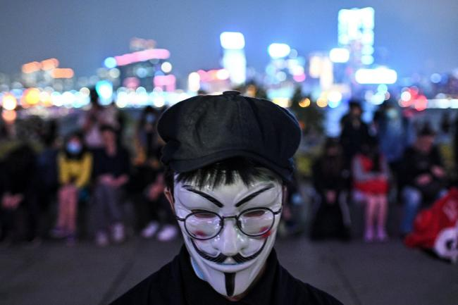 A protester wears the Guy Fawkes mask during a prayer rally in Tamar Park in Hong Kong in memory of university student Alex Chow, 22, who succumbed to head injuries sustained during a fall while demonstrating