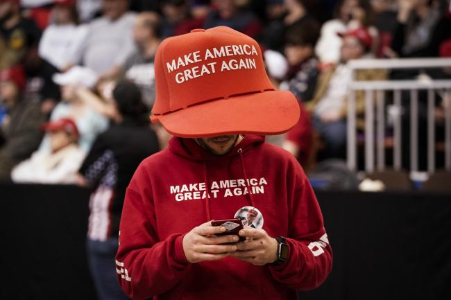 A Trump supporter in an oversize 'Make America Great Again' hat as he waits for the start of a rally in New Hampshire
