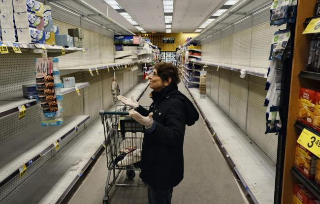 Supermarket shelves are bare as people stock up in preparation for isolation