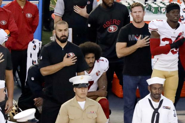 Colin Kaepernick, middle, made famous the 'taking a knee' protest