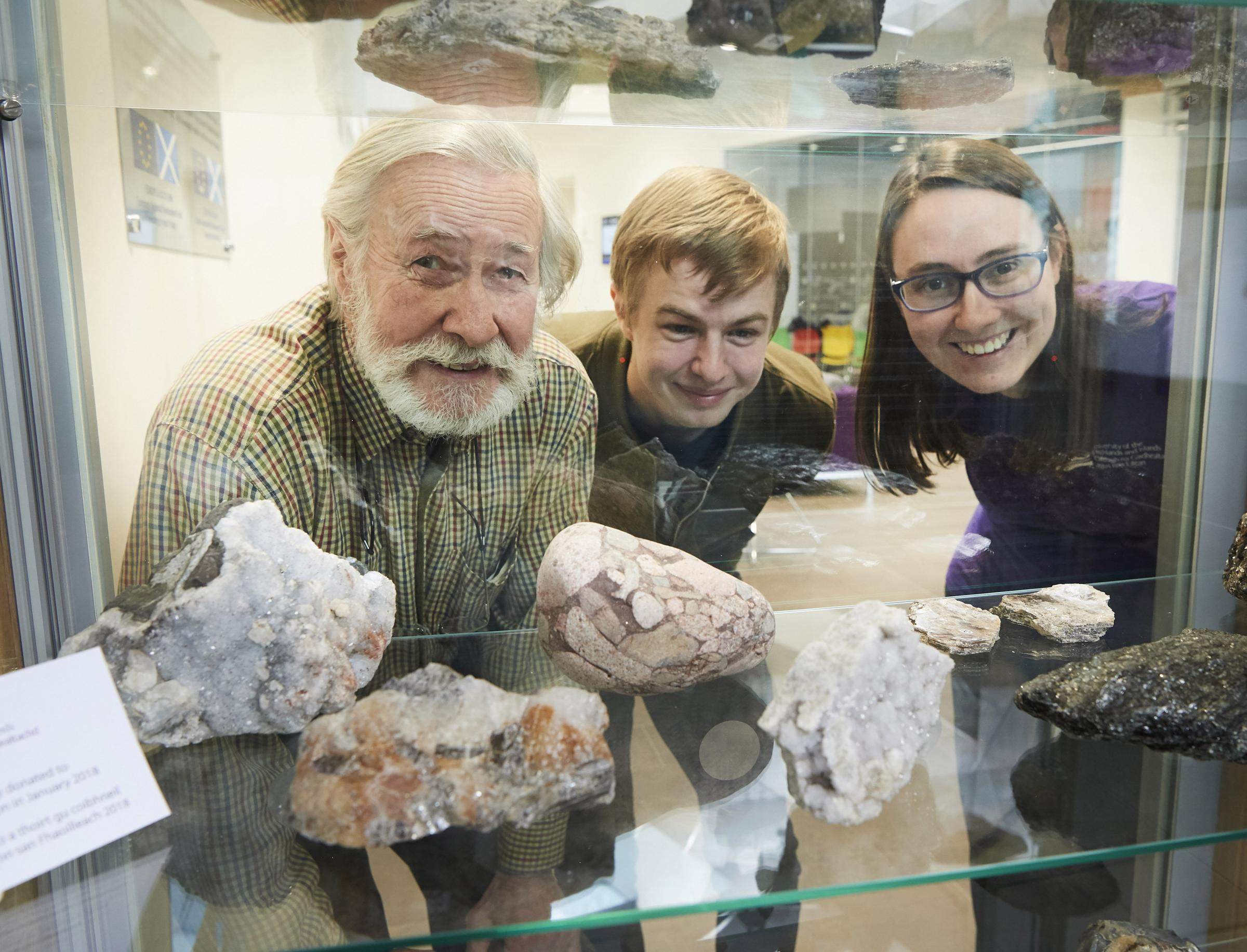 From left: Calum Anton, Keiran Young and Sam Clark with the collection of rock samples gifted to the university