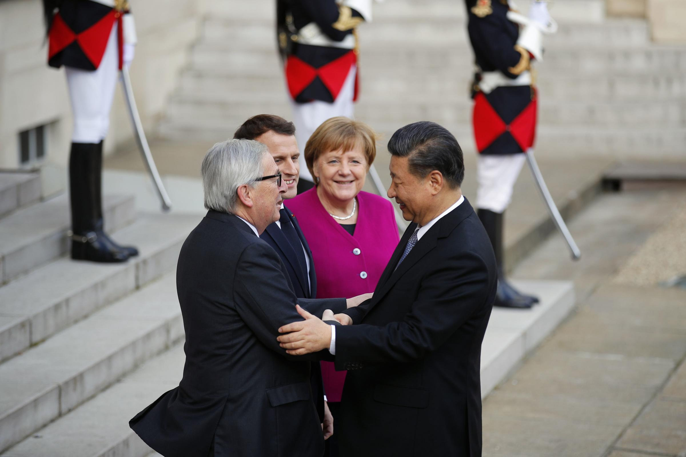 Chinese President Xi Jinping is welcomed by Emmanuel Macron, Angela Merkel, and Jean-Claude Juncker
